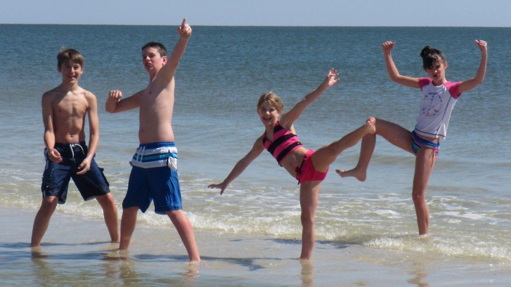 Image of our kids on a Gulf Shores beach in front of one of our vacation houses